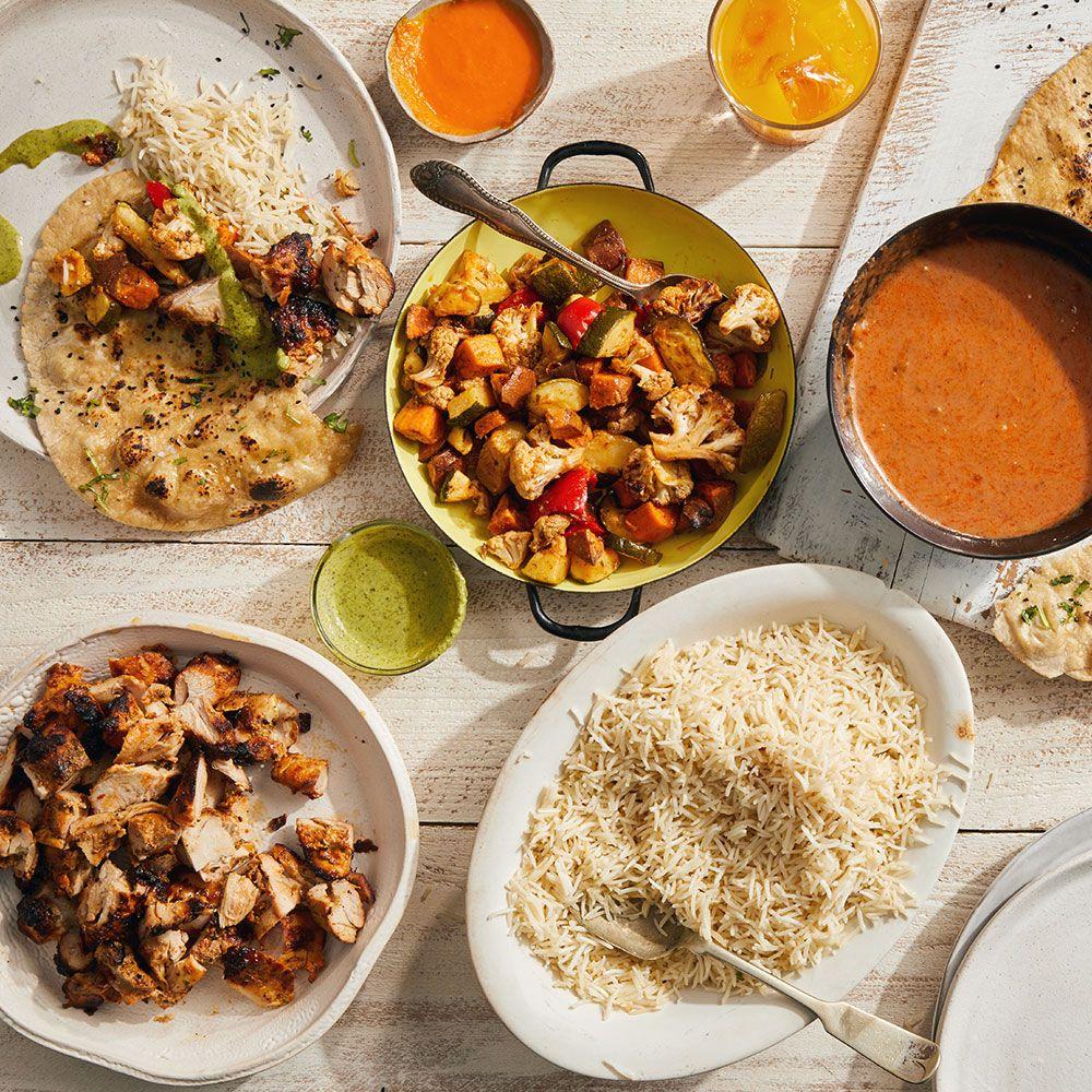 family meal with basmati rice, roasted veggies, tandoori chicken, naan and tikka masala