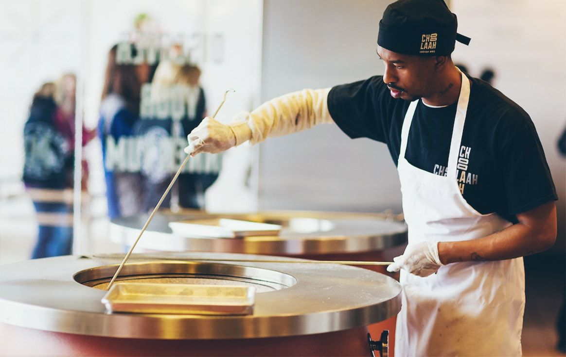 team member cooking in tandoor oven