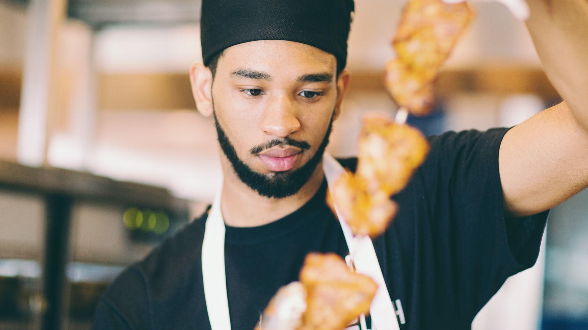 team member holding chicken skewer