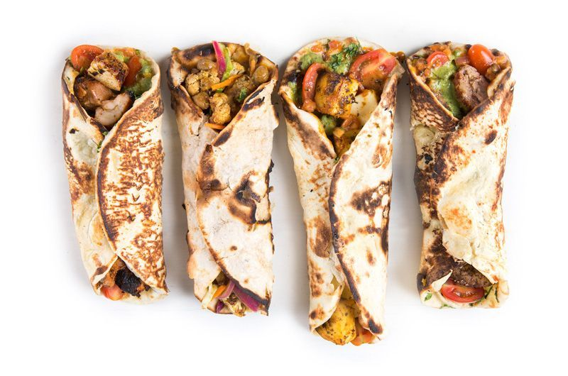 paneer cheese wrap, chicken wrap, vegan wrap and lamb wrap on white background