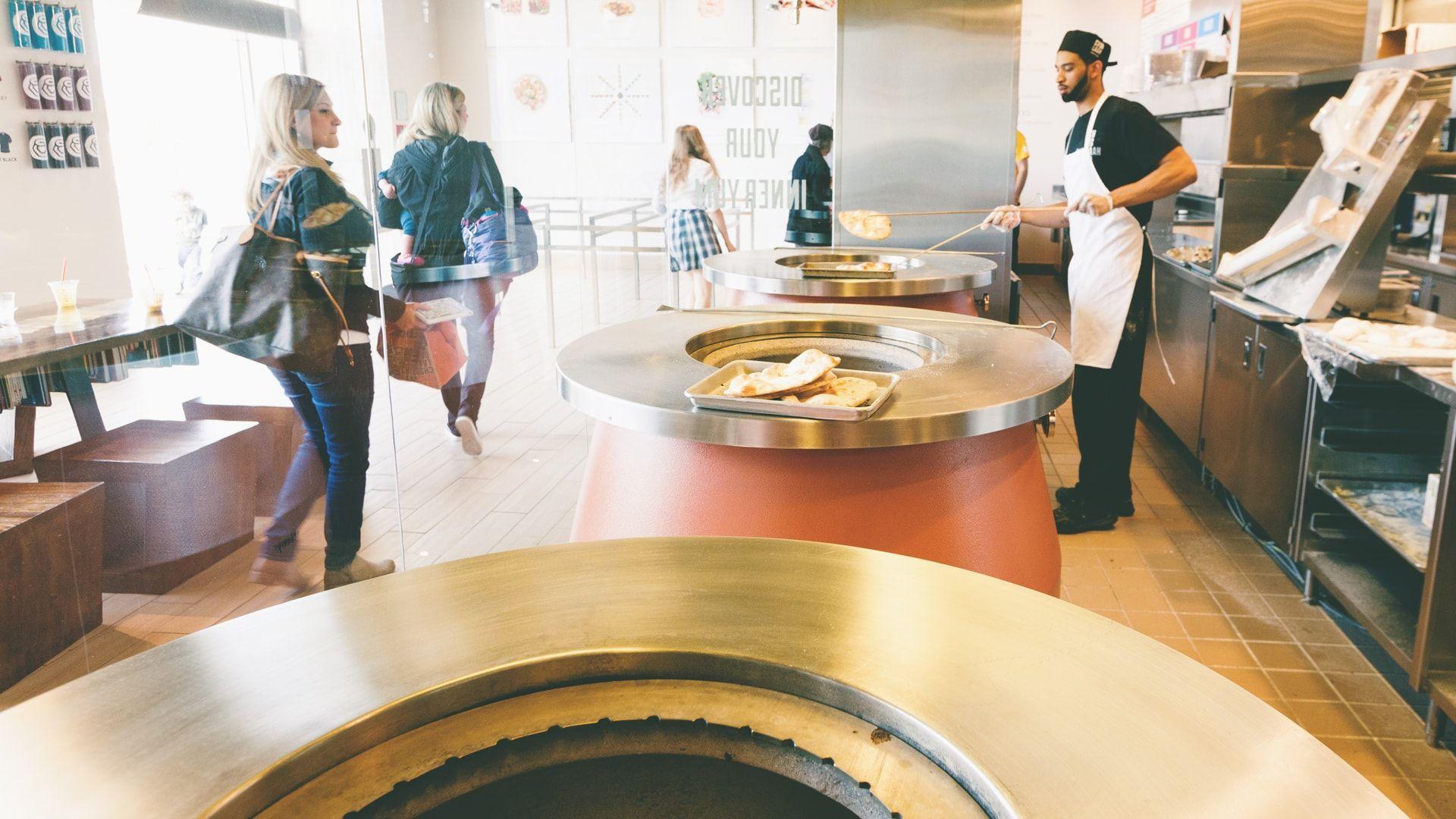 team member making naan in tandoor oven