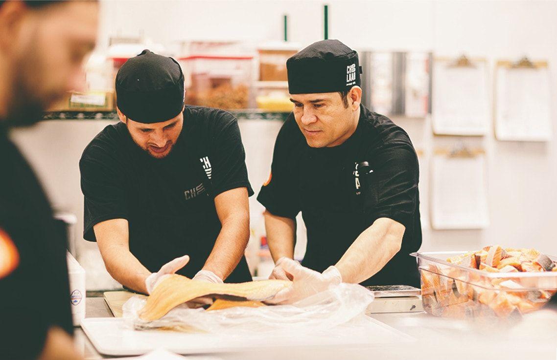 team members cutting salmon