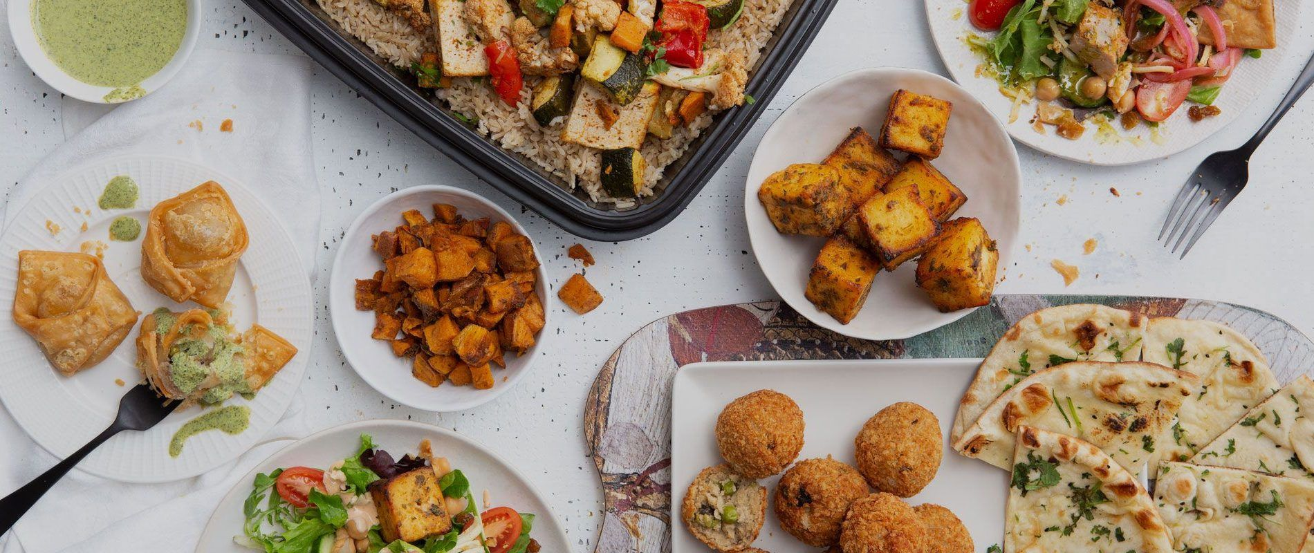 catering meal with samosas, paneer, veggie croquettes, naan and choolaah salad
